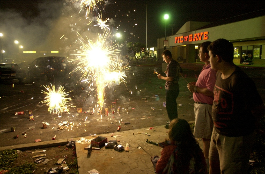 File: A family lights fireworks to celebrate the Fourth of July, 2000, in Santa Ana, where personal fireworks are legal.
