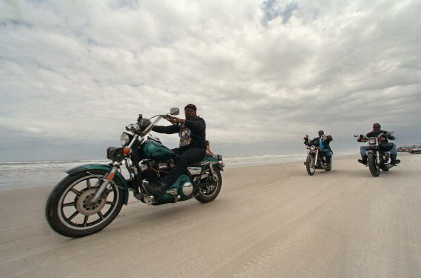 Motorcyclists, one of them on a Harley Davidson (L), roll down the beach along the ocean in Daytona Beach, Florida, 10 March 1995, during Bike Week '95.
