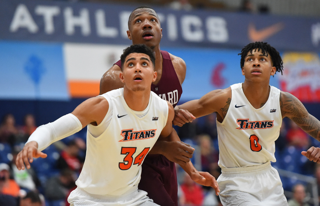In this file photo, Jackson Rowe #34 and Kyle Allman #0 of the Cal State Fullerton Titans and Chris Lewis #0 of the Harvard Crimson wait for a rebound at the Titan Gym on November 26, 2017 in Fullerton, California. The Titans were scheduled Friday to play their first tournament game against Purdue.