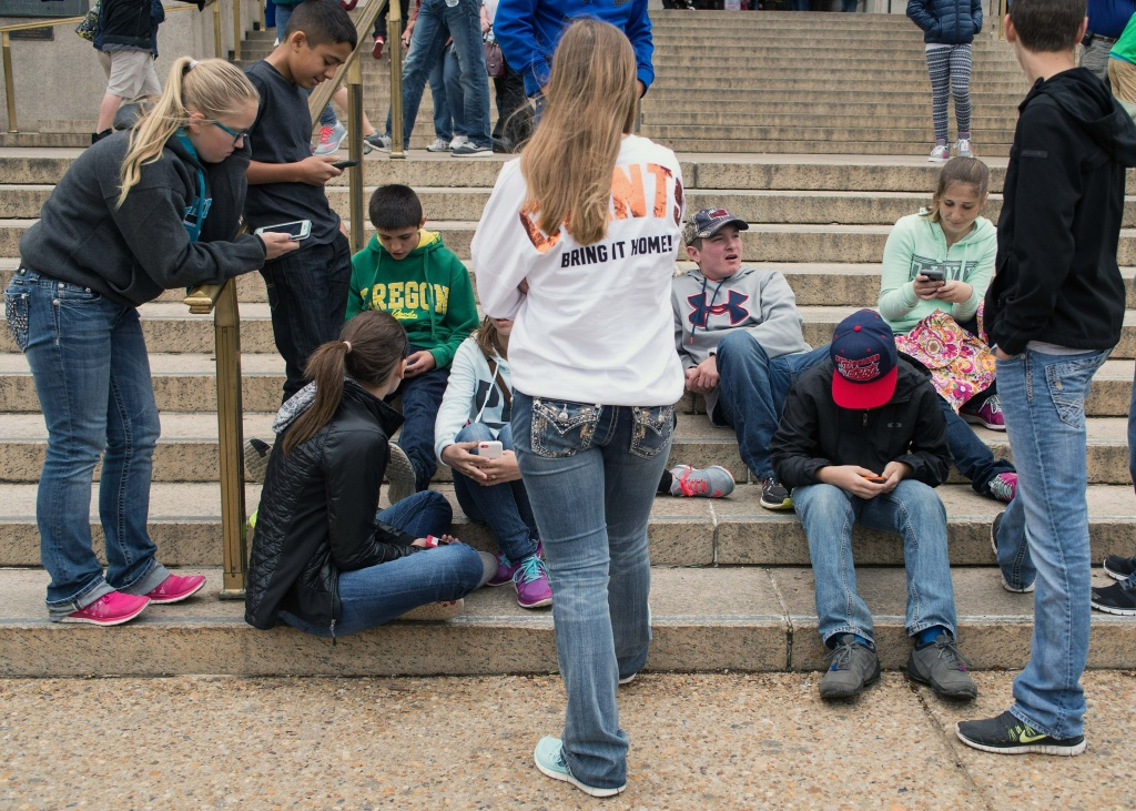 A group of teens check their smartphones outside the Natural History Museum in Washington on April 8, 2015.