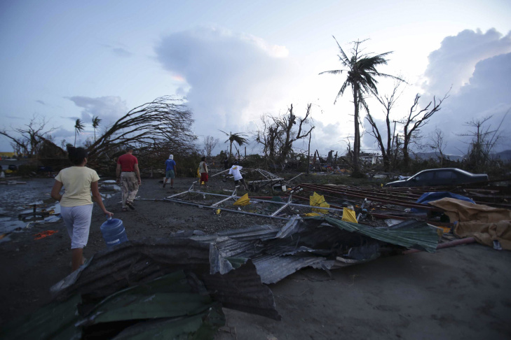 Residents return to their houses after leaving an evacuation site in the aftermath of Super Typhoon Haiyan in Tacloban, eastern island of Leyte on November 9, 2013. One of the strongest typhoons on record killed more than 100 people as savage winds and giant waves flattened communities across the Philippines, authorities said on November 9 while corpses lay amid the devastation.