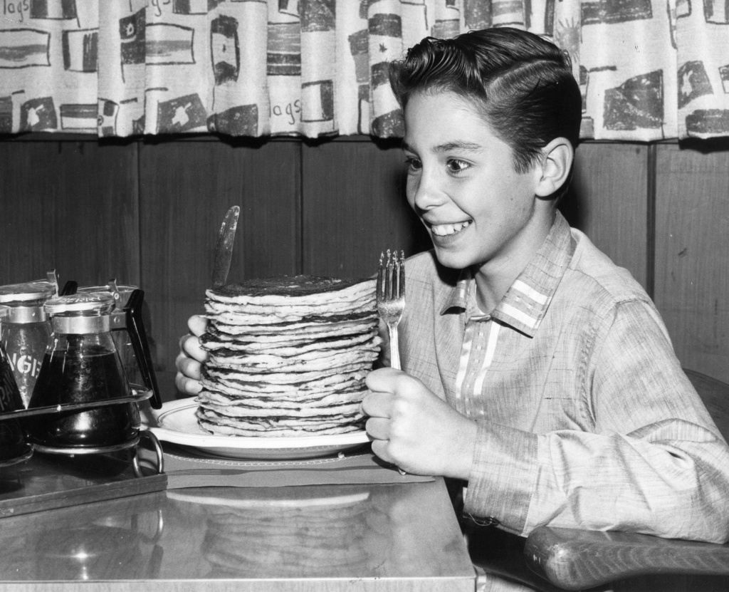 circa 1960: Child actor Johnny Crawford looks forward to eating a pile of pancakes in an International House of Pancakes, a chain of eateries in the USA started in 1958 by Californian brothers Al and Jerome Lapin