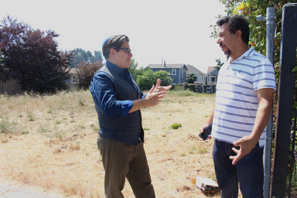 Councilmember Rebecca Kaplan speaks with property owner Francisco Acosta in front of a vacant lot in West Oakland on Aug. 20, 2018. Kaplan authored a proposed tax on vacant properties to help ease homelessness in the city.