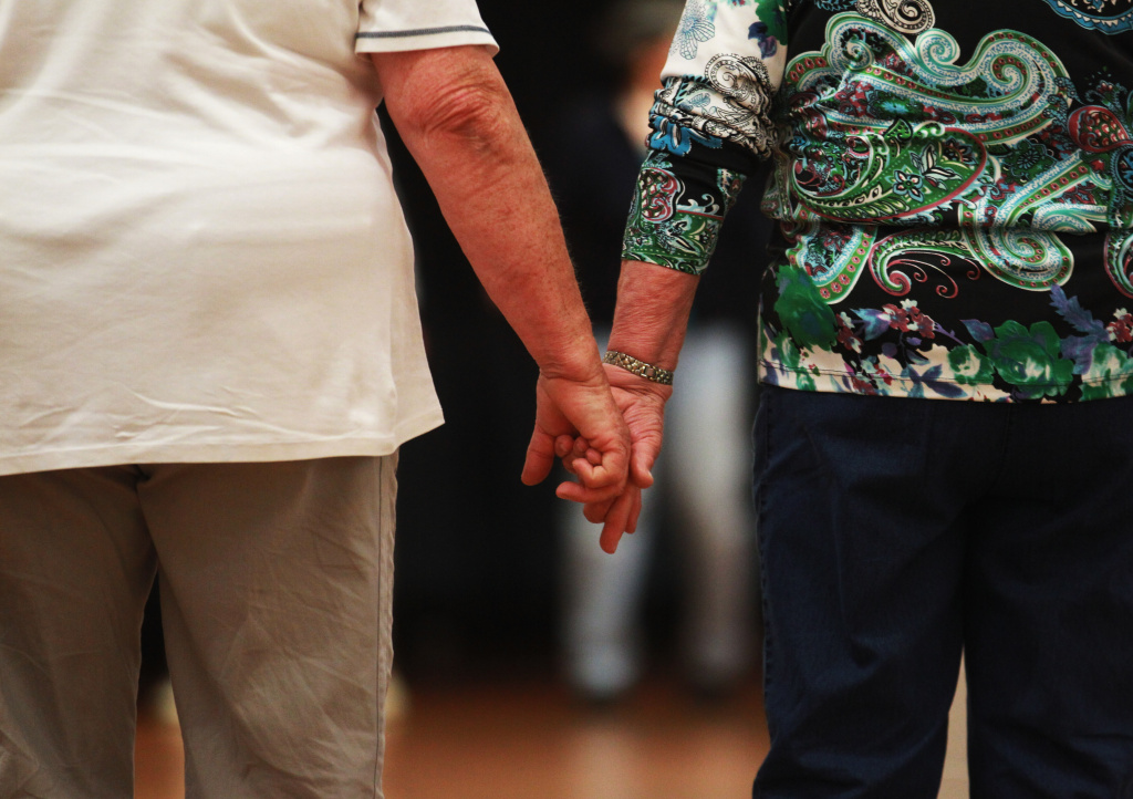 "An elderly couple hold hands at a trade fair at the ""Seniorentag 2012"" senior citizens convention on May 3, 2012 in Hamburg, Germany."