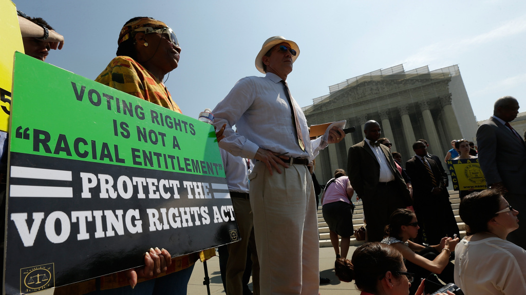 Supporters of the Voting Rights Act listen to speakers discussing the Supreme Court's rulings outside the court building in June 2013. The court ruled that Section 4 of the Voting Rights Act, which aimed at protecting minority voters, is unconstitutional.