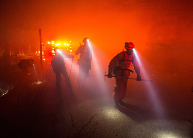 A hand crew member starts a backfire along Baldy Mesa Road late Friday, July 17, 2015,  as the North Fire continues to burn near Interstate 15 in the Cajon Pass in San Bernardino County.