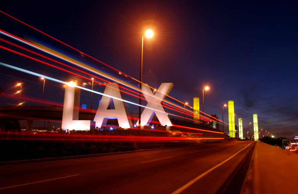 The lights of a shuttle bus streak past the large LAX letters that welcome travelers to Los Angeles International Airport, February 25, 2002, in Los Angeles, CA.