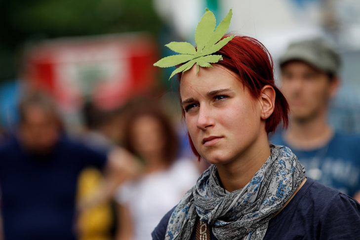 A young woman wearing a paper marijuana leaf on her head marches in support of the legalization of marijuana in Germany.