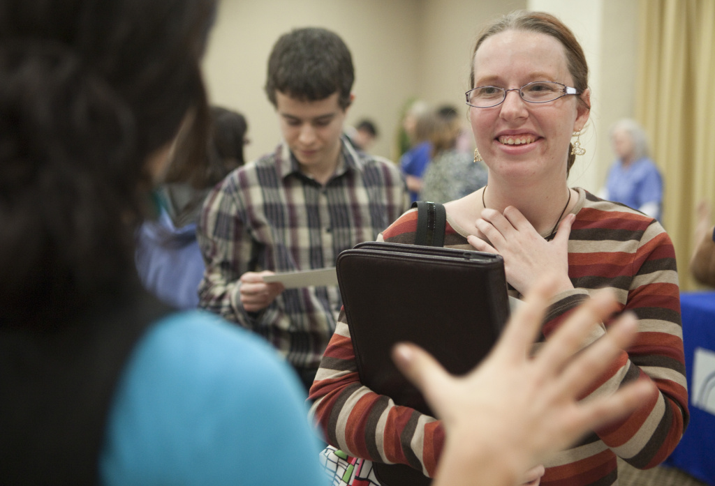 Recent unemployed college graduate Rachel Westrick talks with a potential employer at a job fair.