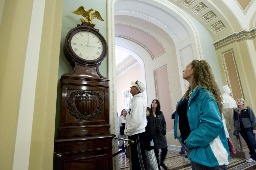 Visitors look toward the Ohio Clock outside the Senate Chamber on Capitol Hill Sunday, Oct. 13, 2013, in Washington. The Ohio Clock has stood watch over the Senate for 196 years. It stopped running shortly after noon Wednesday. Employees in the Office of the Senate Curator ordinarily wind the clock weekly. But they are among the thousands of federal employees furloughed under the partial shutdown. The federal government remains partially shut down and faces a first-ever default between Oct. 17 and the end of the month.
