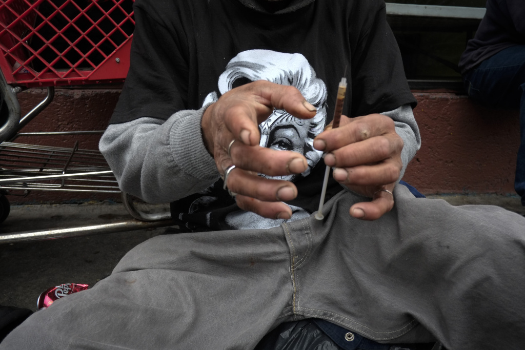FILE - In this Monday, May 6, 2013 file photo, a drug addict prepares a needle to inject himself with heroin in front of a church in the Skid Row area of Los Angeles. It's not a rare scene on Skid Row to spot addicts using drugs in the open, even when police patrol the area. Jim Hall, an epidemiologist who studies substance abuse at Nova Southeastern University in Fort Lauderdale, Fla. says, the striking thing about heroin's most recent incarnation in the early 21st Century, is that a drug that was once largely confined to major cities is spreading into suburban and rural towns across America, where it is used predominantly by young adults between the ages of 18 and 29.