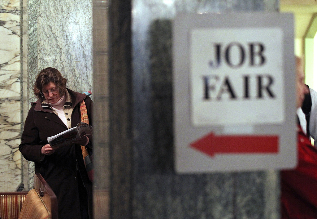A job seeker looks over event materials as she waits to enter the San Francisco Hirevent job fair at the Hotel Whitcomb in San Francisco. Two encouraging if not exactly thrilling reports on hiring and layoffs arrived this morning, ahead on Friday's official government jobs numbers.