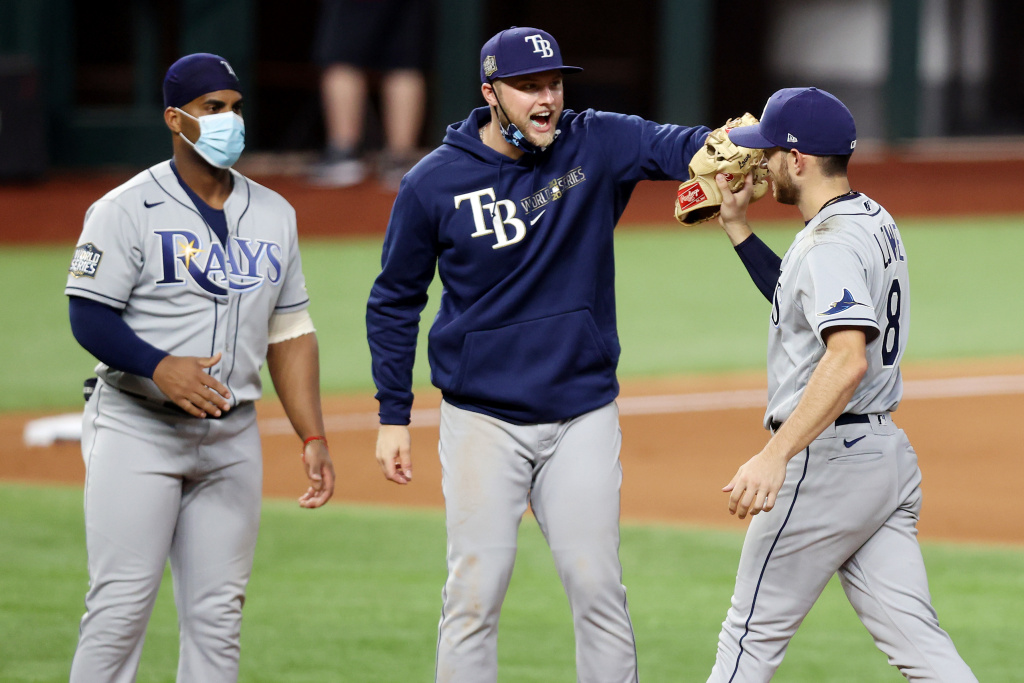 Yandy Diaz #2, Austin Meadows #17 and Brandon Lowe #8 of the Tampa Bay Rays celebrate the teams 6-4 victory against the Los Angeles Dodgers in Game Two of the 2020 MLB World Series at Globe Life Field on October 21, 2020 in Arlington, Texas.