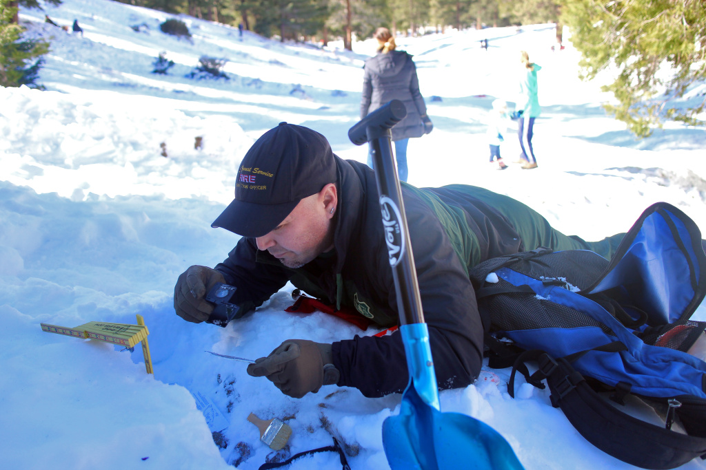 Nathan Judy examines the snow at Manker Flats in the Angeles National Forest. Snow rangers identify areas that may be at risk of avalanche.