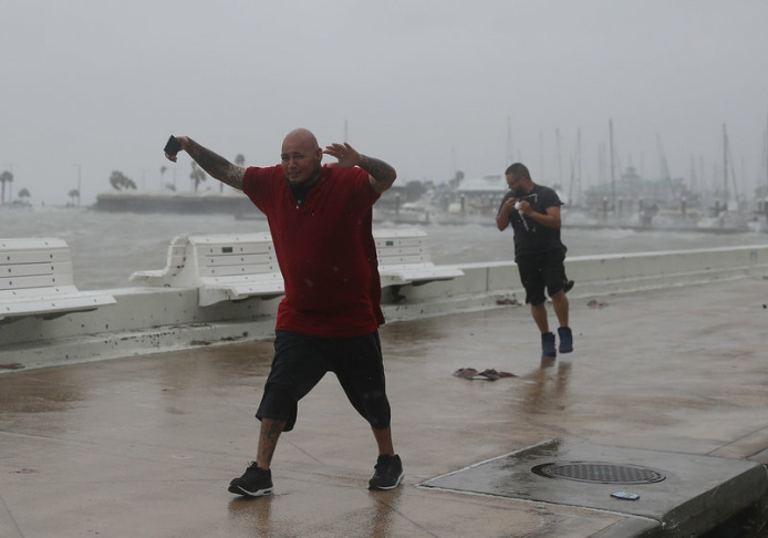 Raul Barral (left) and Carlos Guerra walk through high wind and driving rain in Corpus Christi, Texas, Tuesday as Hurricane Harvey approaches the Gulf Coast.
