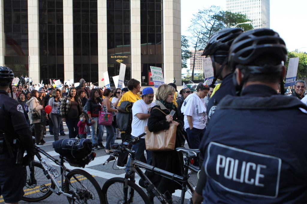 Protesters cross Hope Street bordered by police and make their way to Wells Fargo Center