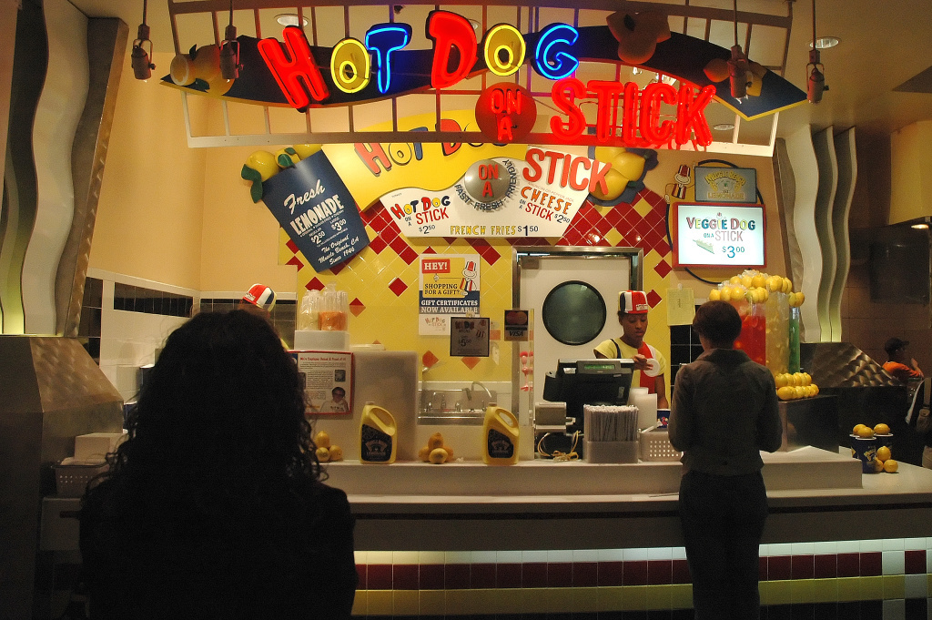 In this Creative Commons licensed photo, a clerk in the colorful Hot Dog on a Stick uniform takes a customer's order. HDOS Enterprises, which owns the iconic restaurant chain, announced Monday that it has filed a Chapter 11 bankruptcy petition.