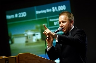 An auctioneer notes a bid on a foreclosed home during an auction on in Denver, Colorado.