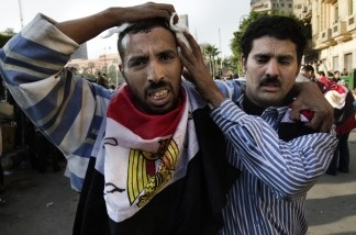An Egyptian anti-regime protester wounded during clashes with government supporters is escorted by a fellow demonstrator to get medical treatment at a makeshift clinic at the Ibad al-Rahman mosque near the flashpoint Tahrir square in Cairo on Feb. 2, 2011.