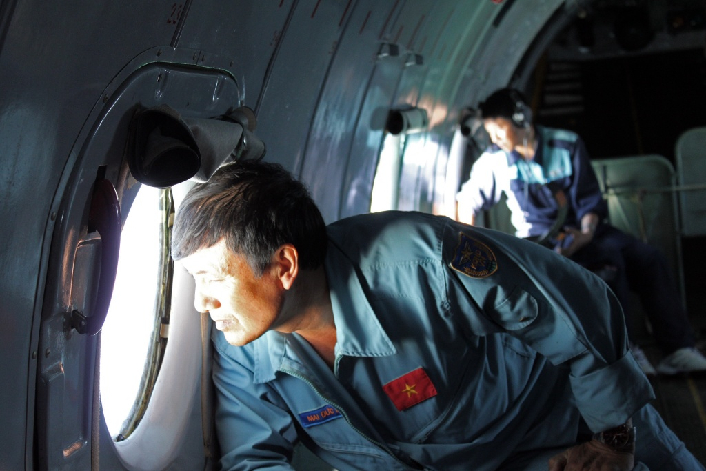This picture taken on March 8, 2014 shows military personnel scanning the sea aboard a Vietnamese Air Force aircraft taking part in a search mission for a missing Malaysia Airlines aircraft, somewhere between Malaysia's east coast and southern Vietnam. Malaysia Airlines said on March 9 that it was 'fearing the worst' for the passenger jet that vanished carrying 239 people, as search teams hunt for the plane.