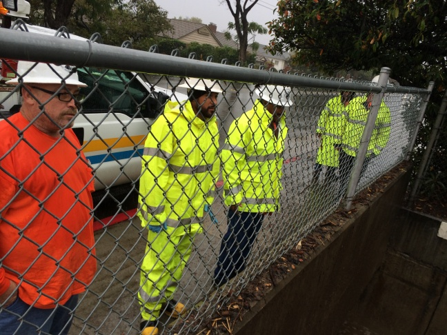 County workers use heavy equipment to break up debris flow in Glendora during a winter storm.