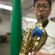 Adolfo Ramos, a senior at the music academy at Hamilton High, demonstrates a baritone saxophone that is not in playable condition. It has broken keys and the sax is held together with tape.