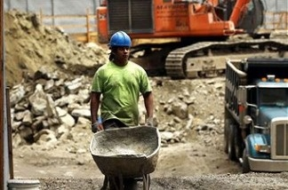 A worker pushes a wheelbarrow on a construction site.