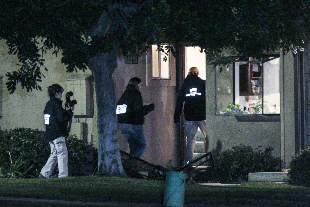 FBI agents search outside a home in connection to the shootings in San Bernardino, Thursday, Dec. 3, 2015, in Redlands, Calif.. A heavily armed man and woman opened fire Wednesday on a holiday banquet, killing multiple people and seriously wounding others in a precision assault, authorities said. Hours later, they died in a shootout with police.