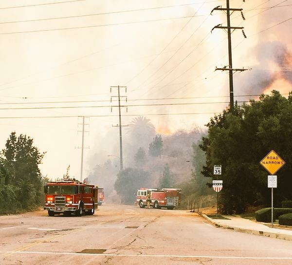 A brush fire burns in a riverbed in Montebello Sunday afternoon.