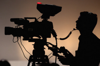 A silhouette of a camera operator shooting film. File photo.