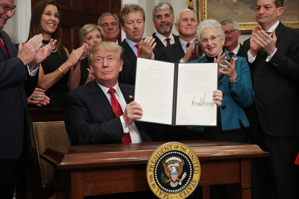 President Donald Trump shows an executive order after he signed it Thursday as Sen. Rand Paul (R-KY), Vice President Mike Pence, Rep. Virginia Foxx (R-NC) and Secretary of Labor Alexander Acosta look on during an event in the Roosevelt Room of the White House.