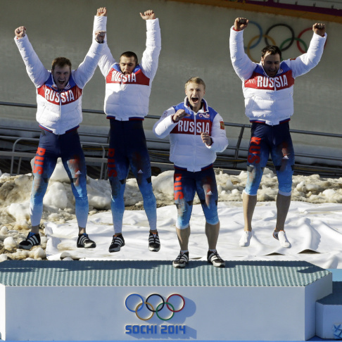 Russia RUS-1 bobsled team, with Alexander Zubkov, Alexey Negodaylo, Dmitry Trunenkov, and Alexey Voevoda, jump onto the medal stand after winning gold on Sunday. On the last day of the Sochi Games, Russia had already secured the top spot in the overall me