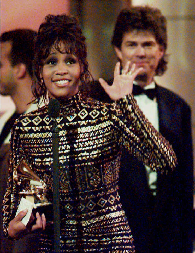 Whitney Houston waves to the crowd at the 36th Annual Grammy Awards in New York 01 March 1994 after she was honored for Record of the Year, 'I'll Always Love You,' and Album of the Year, the soundtrack from the film 'The Bodyguard.'
