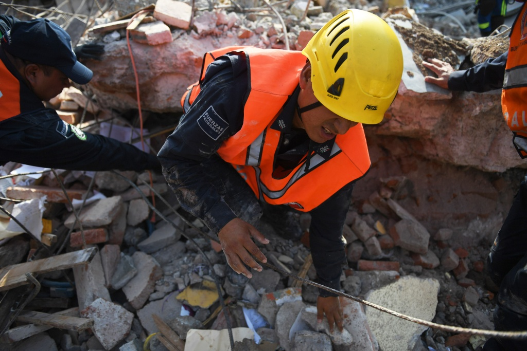 A member of the Federal Police's rescue team searches for survivors in Juchitan de Zaragoza, Mexico, on September 9, 2017 after a powerful earthquake struck Mexico's Pacific coast.