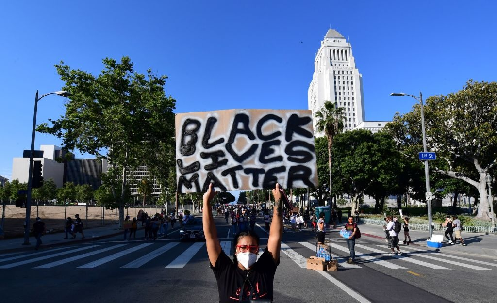 A protesters holds up a placard past City Hall during a march to protest the death of George Floyd under police custody, in downtown Los Angeles, California on June 3, 2020. - Derek Chauvin, the white Minneapolis police officer who kneeled on the neck of George Floyd, a black man who later died, will now be charged with second-degree murder, and his three colleagues will also face charges, court documents revealed on June 3. The May 25 death of George Floyd -- who had been accused of trying to buy cigarettes with a counterfeit bill -- has ignited protests across the United States over systemic racism and police brutality. (Photo by Frederic J. BROWN / AFP) (Photo by FREDERIC J. BROWN/AFP via Getty Images)