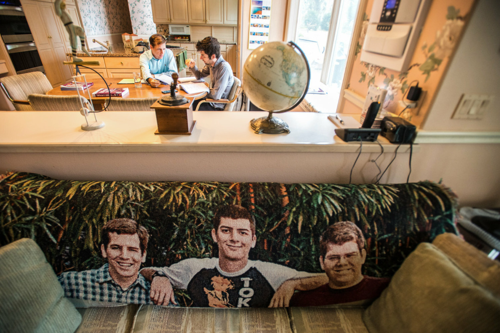 Charles (right) gets tutoring from his brother David on the GRE test at their parents' home. The couch in the living room bears a blanket with images of the three Mayer brothers.