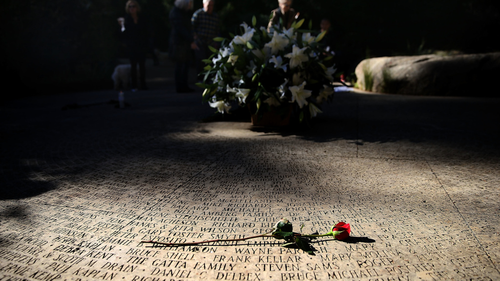 A flower lays on the engraved names of AIDS victims at the National AIDS Memorial Grove on December 1, 2015 in San Francisco, Calif.