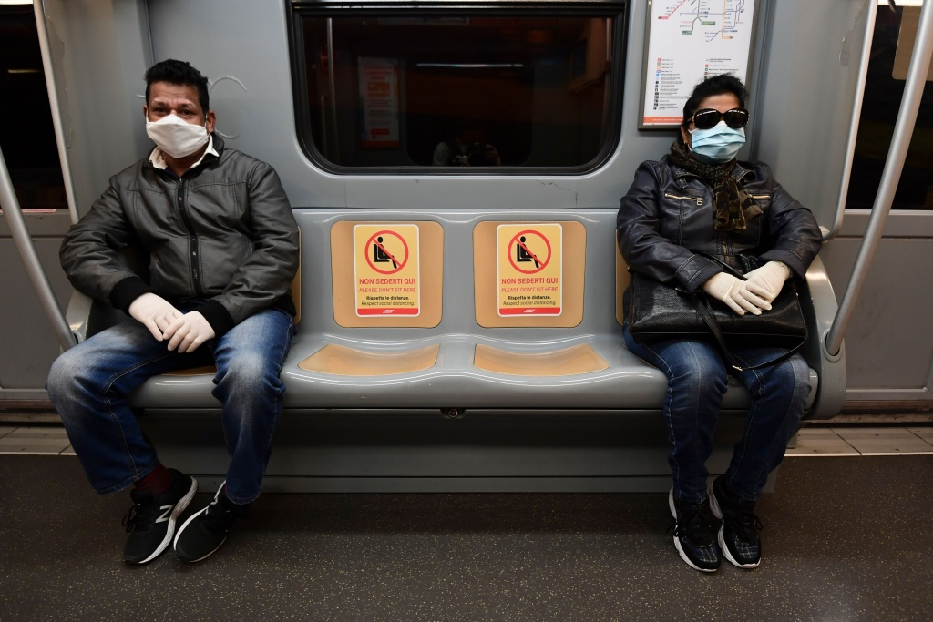 Commuters maintaining distance sit next to seats with stickers reading