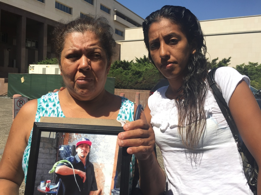 Mona Martinez (left) holds a photo of her son David Coborubio, who was fatally shot by an FBI agent in August.