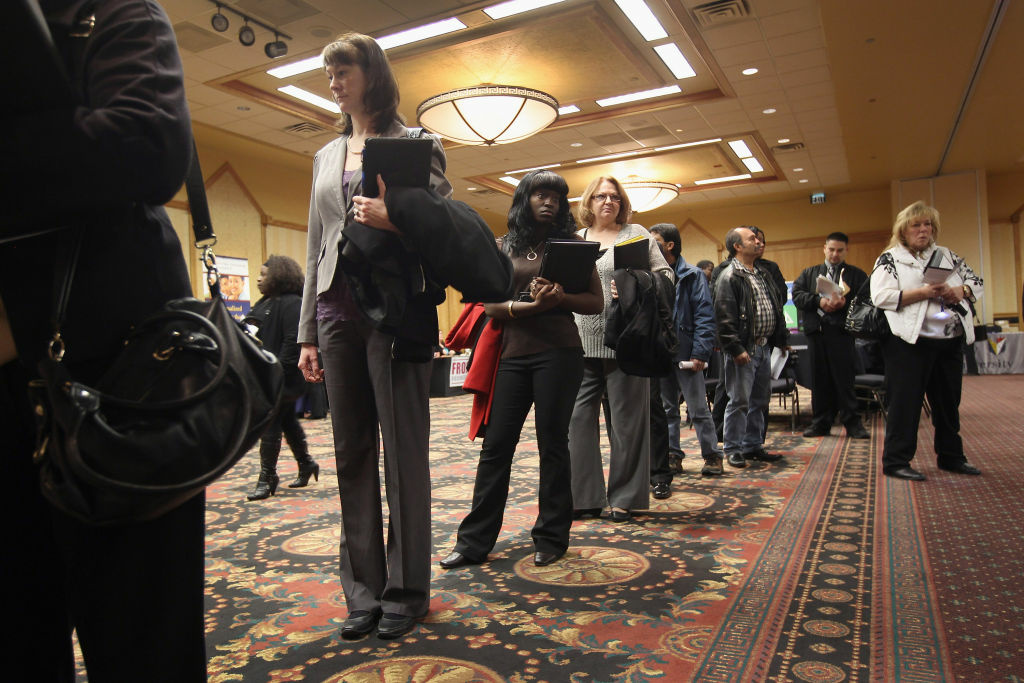 Job applicants wait in line to meet potential employers at the