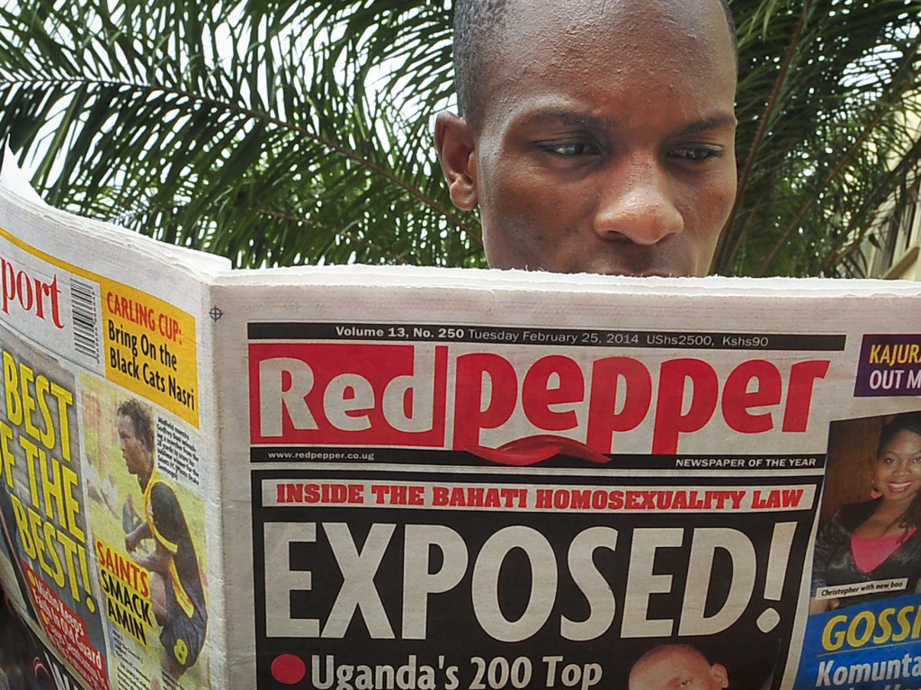 A Ugandan reads a copy of the <em>Red Pepper</em> tabloid newspaper in Kampala, Uganda, on Tuesday. The newspaper published a list Tuesday of what it called the country's