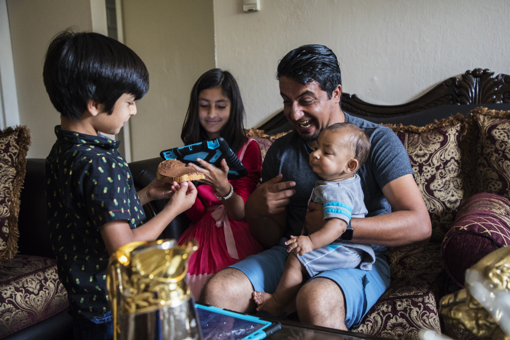 Khisrow Jan, a refugee from Afghanistan, lives in a cramped apartment in Antioch with his wife and their four children. He drives an Uber more than 70 hours a week to make ends meet.