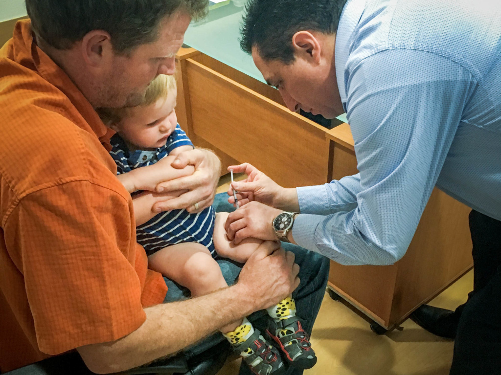 Erik Vance holds his son while the pediatrician administers vaccinations.