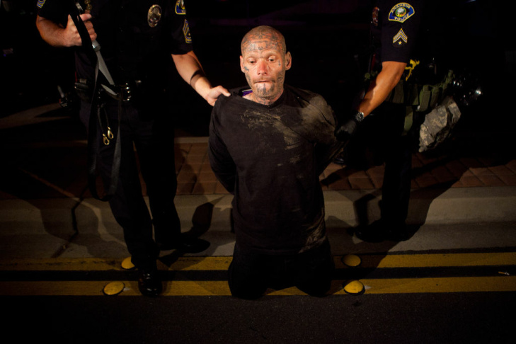 A protester kicks a passing police car during a demonstration to show outrage for the shooting death of Manuel Angel Diaz, 25, at Anaheim City Hall on July 24, 2012 in Anaheim, California.