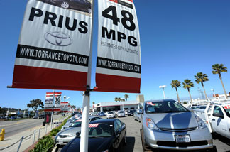 Prius (R) and other Toyota cars are on display at a Toyota dealership in Torrance.