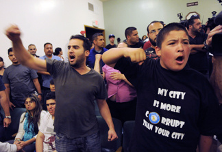 Bell, Calif. residents Hussein Saleh, left, and Eddie Delgado call for the ouster of city officials during a special meeting of the Bell City Council, Thursday, July 22, 2010, in Bell, Calif. Bell's police chief and two top city administrators agreed to resign Thursday night during a closed-door meeting at City Hall. Revelations about Bell city leaders' pay has sparked anger in a blue-collar town that is one of the poorest in Los Angeles County.