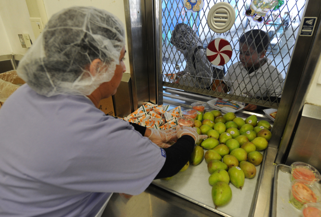 A school cafeteria worker hands out fruit and drinks to students at an elementary school in South Los Angeles in this December 2, 2010 file photo. The California Assembly on Wednesday will consider a plan to give unemployment benefits to cafeteria workers, janitors and other classified workers during the summer months, when there isn't much work.