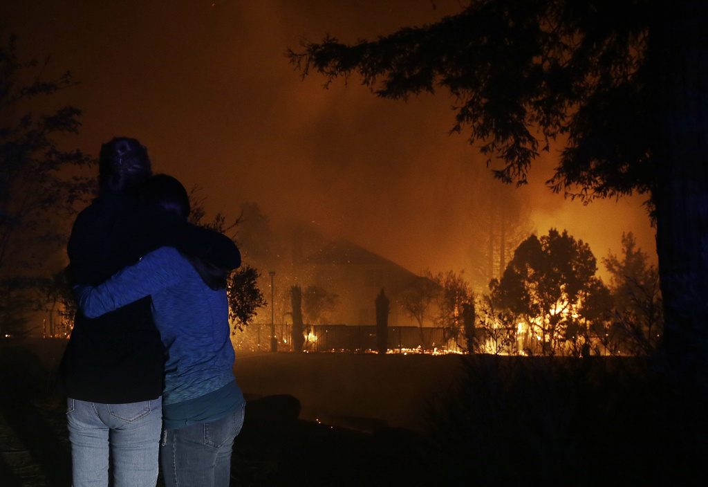 Two women hug as they watch houses burn in Santa Rosa, California on October 9, 2017.