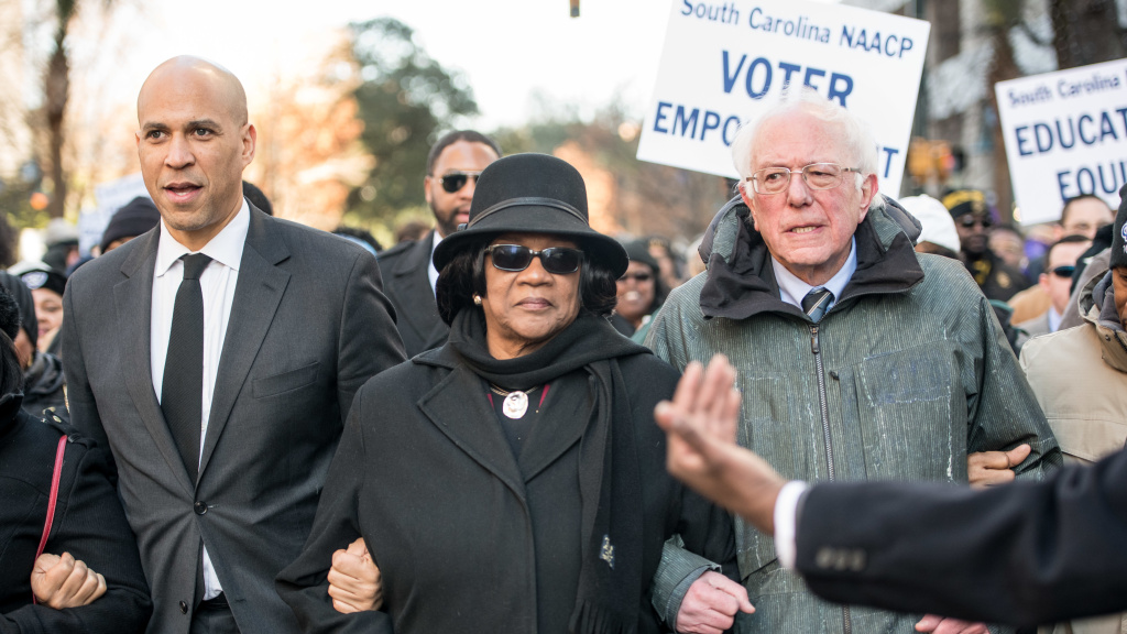 Democratic Sens. Cory Booker and Bernie Sanders, seen at a South Carolina NAACP march in January, are two of the 2020 presidential candidates pressed on the issue of reparations this week.
