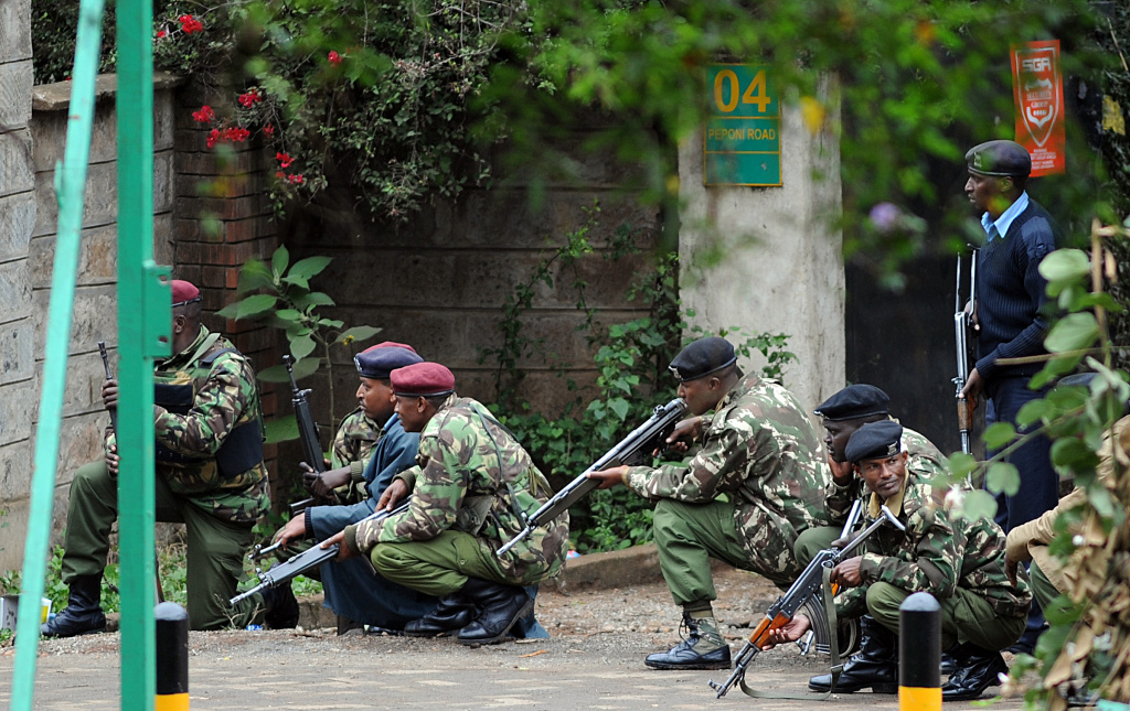 Armed Kenyan policemen take cover outside the Westgate mall in Nairobi on September 23, 2013. Kenyan troops were locked in a fierce firefight with Somali militants inside an upmarket Nairobi shopping mall on September 22 in a final push to end a siege that has left at least 69 dead and 200 wounded with an unknown number of hostages still being held.